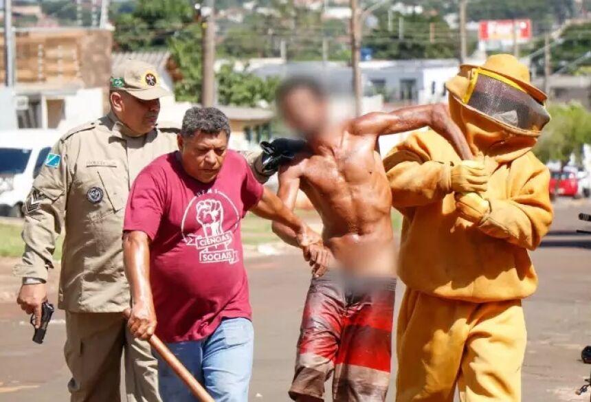 Morador (de camisa vermelha) e bombeiros tentam conter o suspeito (Foto: Henrique Kawaminami) - CREDITO: CAMPO GRANDE NEWS