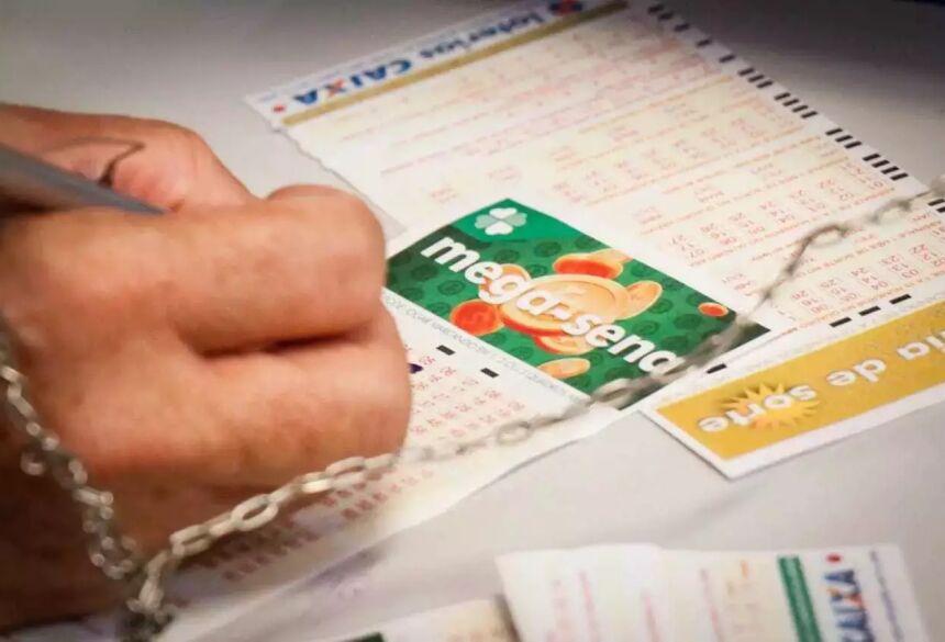 Apostador anota números em talão da Mega-Sena. (Foto: Arquivo / Campo Grande News)